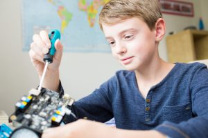 Boy Assembling Robotic Kit In Bedroom